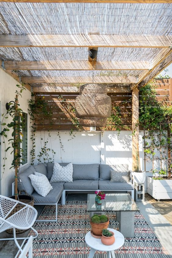 a bright boho patio with a corner sofa, some metal chairs, a concrete and marble table, a wicker pendant lamp and some greenery on the walls