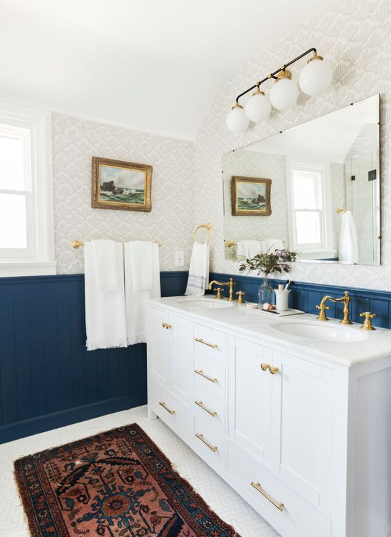 a bright eclectic bathroom with bold blue beadboard, neutral printed wallpaper, a white vanity and touches of brass
