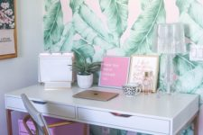 a bright tropical home office nook with a tropical leaf wall, a pink storage unit and art and touches of gold and brass