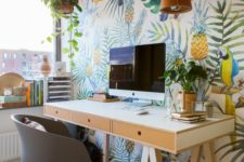 a bright tropical home office with a super bold accent wall, a cork lamp, some plants, a trestle desk and a grey chair