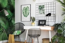 a bright tropical home office with a tropical leaf wall, lots of potted greenery, artworks, a woven basket and hanging bulbs
