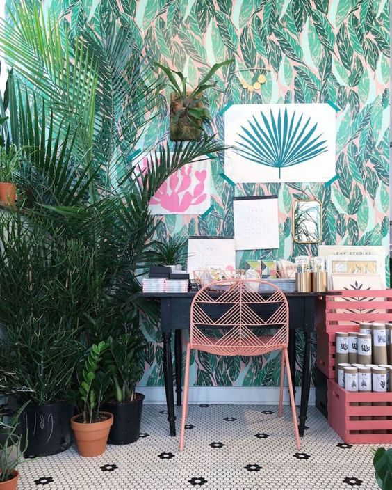 a bright tropical home office with tropical wallpaper, bright artworks and potted plants, a vintage desk and pink furniture