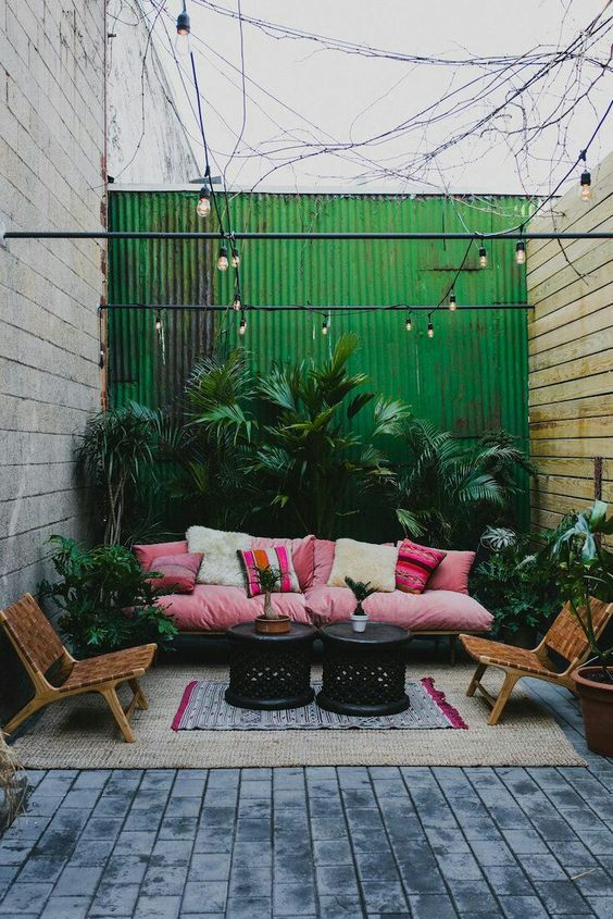 a bright tropical patio with a pink sofa and printed pillows, leather chairs, lots of lush plants in pots and black tables