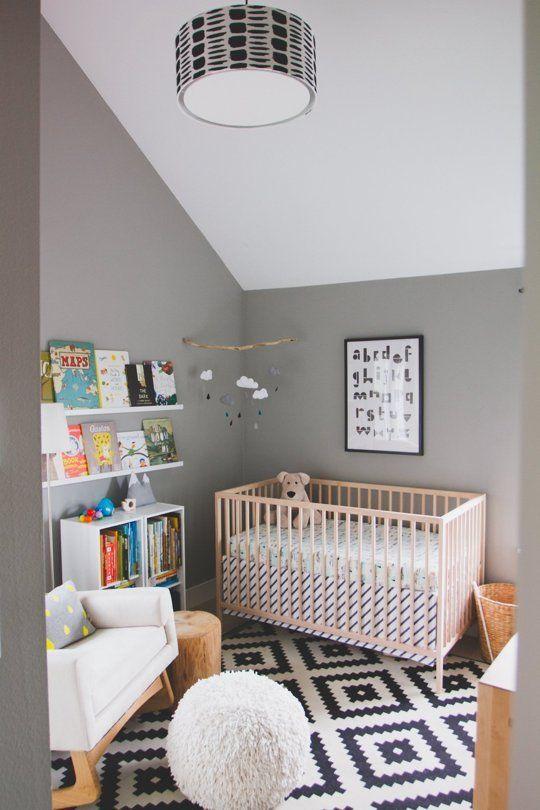 a casual nursery with grey walls and a white ceiling, a printed rug, simple furniture and a bookshelf for reading to your kid