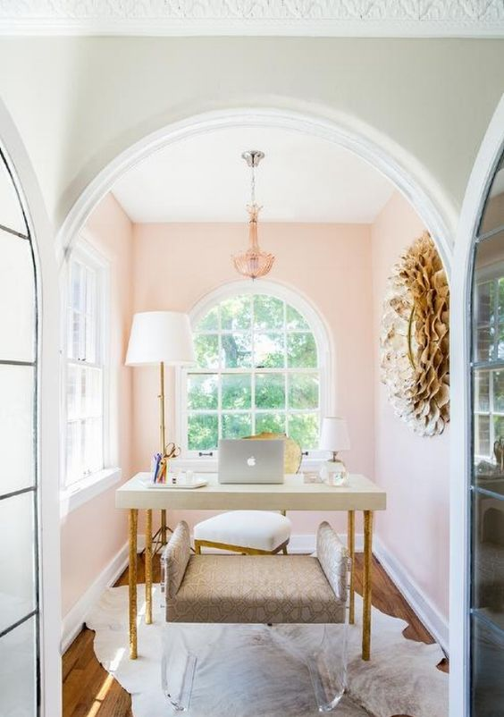 a chic and cozy home office nook with light pink walls, a chic chandelier, a simple desk and an upholstered and acrylic bench