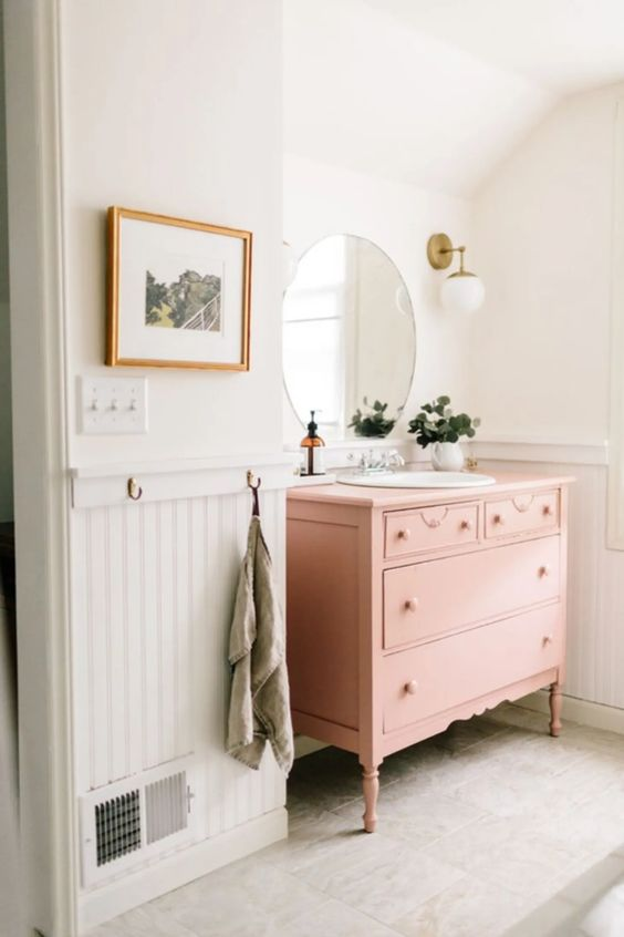 a chic and cute bathroom with white beadboard, a pink vanity, a round mirror, potted greenery and sconces is ethereal