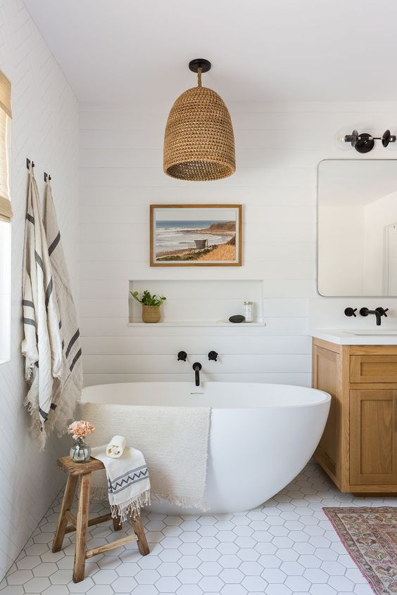 a chic beach bathroom done with a white beadboard wall, hex tiles, a wicker lamp and a wooden vanity plus touches of black