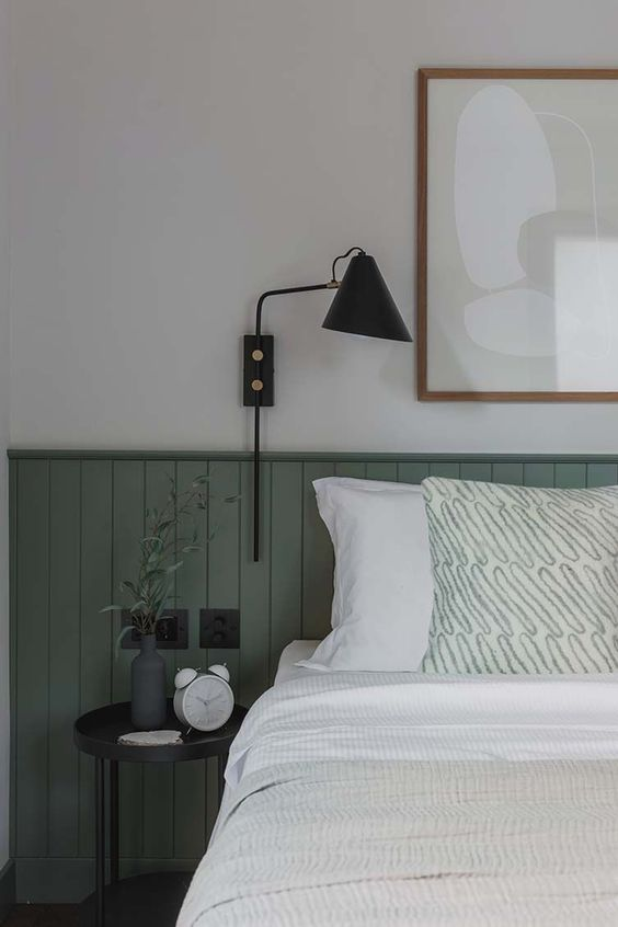 a chic bedroom with green beadboard, a black nightstand and sconce, a neutral artwork and some accessories