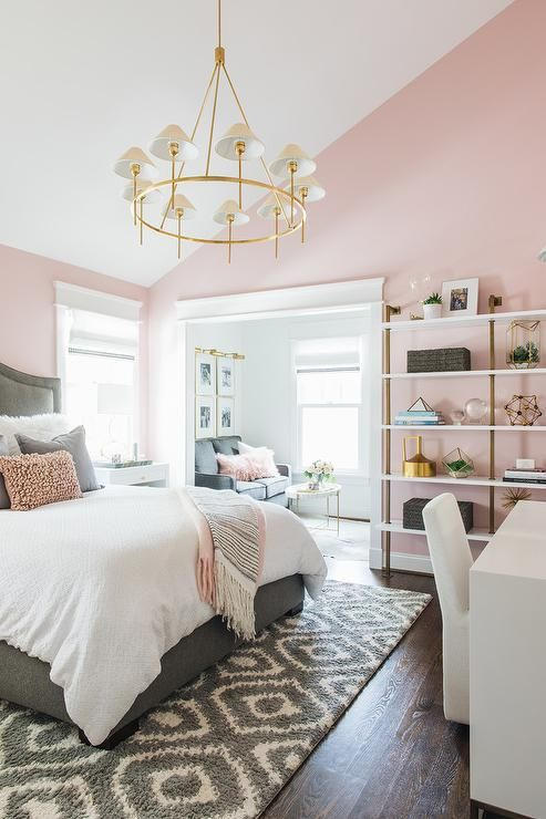 a chic bedroom with pink walls, pink pillows and a blanket, touches of gold and brass for a glam feel