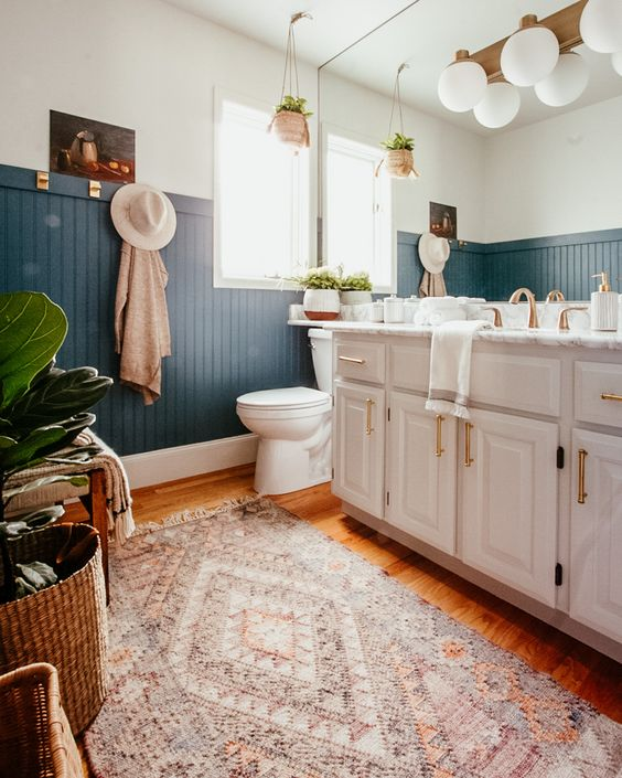 a chic boho bathroom with blue beadboard, a large vanity and a mirror wall, potted plants and layered rugs