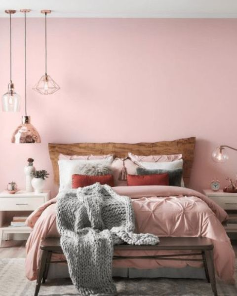 a chic contemporary bedroom with a pink statement wall, pink bedding, grey touches, pendant lamps and white furniture