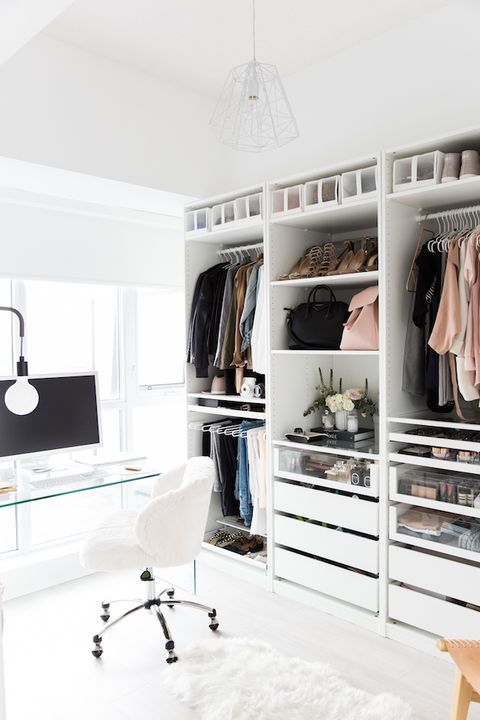 a chic contemporary cloffice with a white amekshift closet, drawers, some open shelves, a sheer glass desk, a white chair and an ethereal lamp