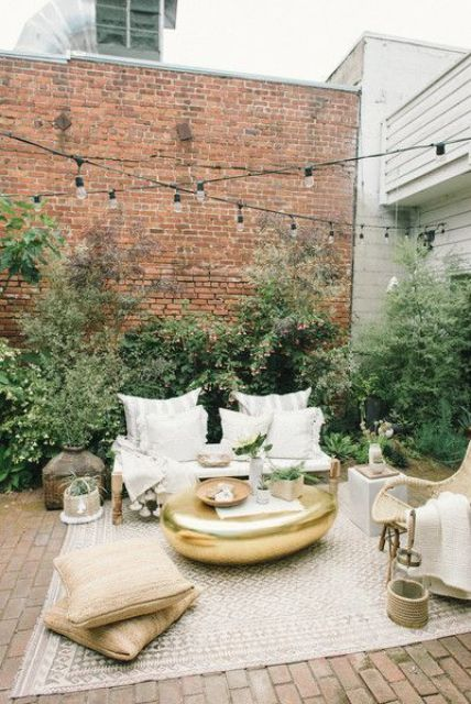 a chic small patio with a rug, some pillows, potted greenery, baskets and wooden and wicker furniture