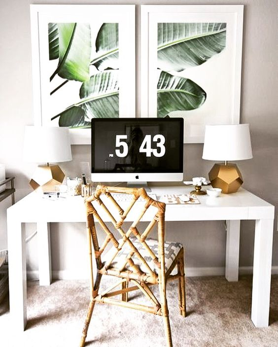a chic tropical home office nook with a rattan chair, gold table lamps, tropical artworks and a white desk
