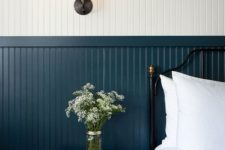 a chic vintage-inspired bedroom with white and navy beadboard fully covering the wall, a black forged bed and a wooden nightstand