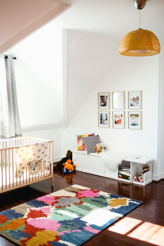 a colorful attic nursery with a pink ceiling, a gallery wall, bright printed textiles and a wicker pendant lamp