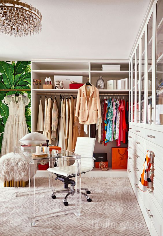 a colorful glam cloffice with a crystal chandelier, a printed rug, a makeshift closet, a largre closed storage unit, an acrylic desk and a white chair