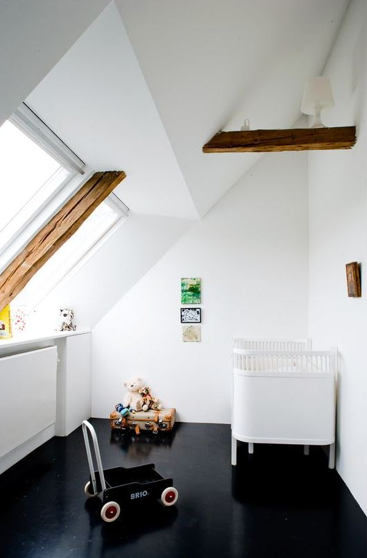 a contrasting attic nursery with a black floor, wooden beams, a white crib, some toys and a bright galley wall