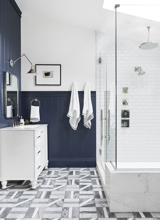 a contrasting bathroom with white tiles, navy beadboard, a skylight and printed tiles on the floor plus a white vanity