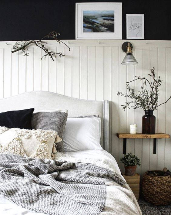 a contrasting bedroom with black walls, white beadboard, an upholstered bed, wooden and wicker touches and branches