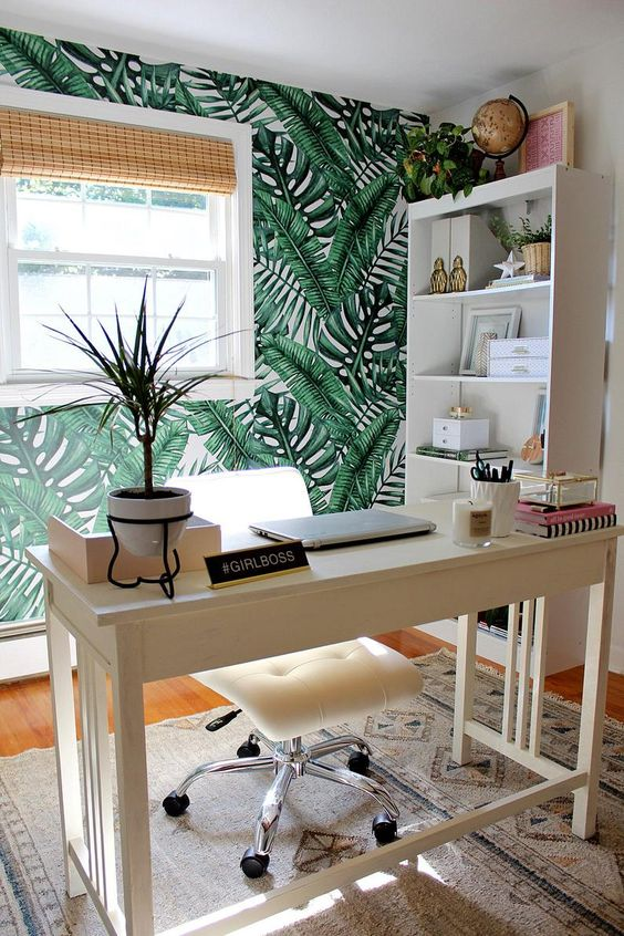 a cool and inviting tropical home office with a tropical leaf wall, woven shades, a tropical plants and touches of pink