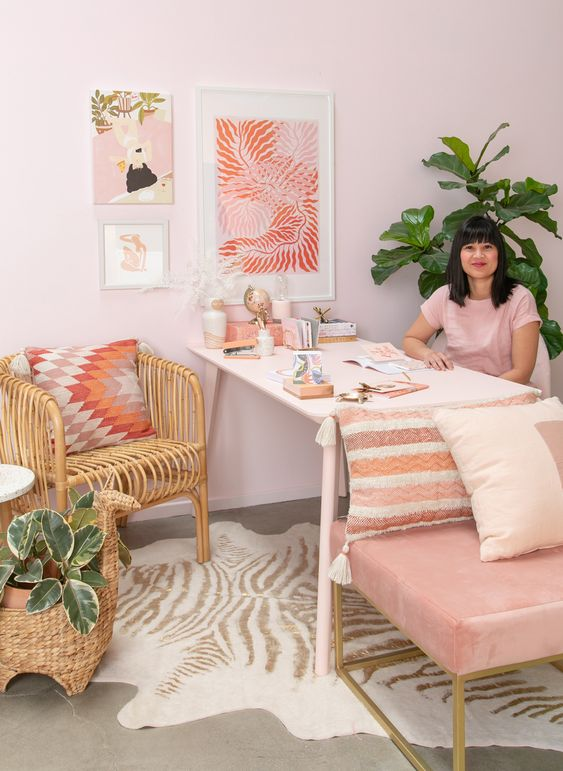 a cool glam home office with light pink walls, a pink chair, a pink gallery wall and a bright printed pillow