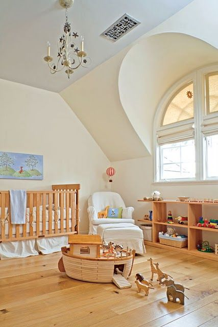 a cozy and simple attic nursery with a blue ceiling, wooden furniture, toys and a vintage chandelier