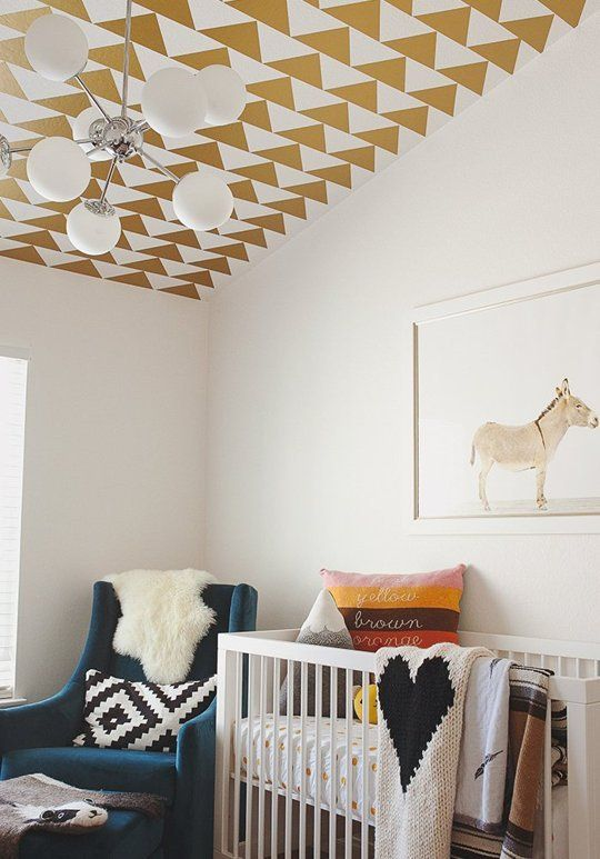 a cozy nursery with a geometric printed ceiling, bright printed textiles, a blue chair and a fun artwork