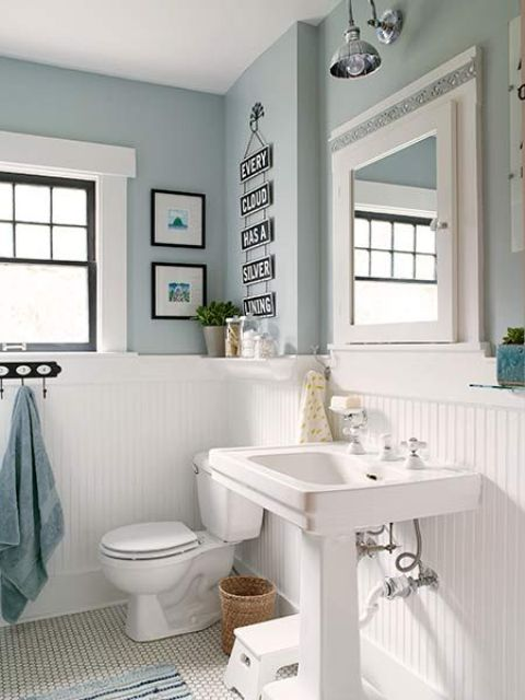 a cozy vintage farmhouse bathroom with light blue walls, white beadboard, a free standing sink, some art and much light