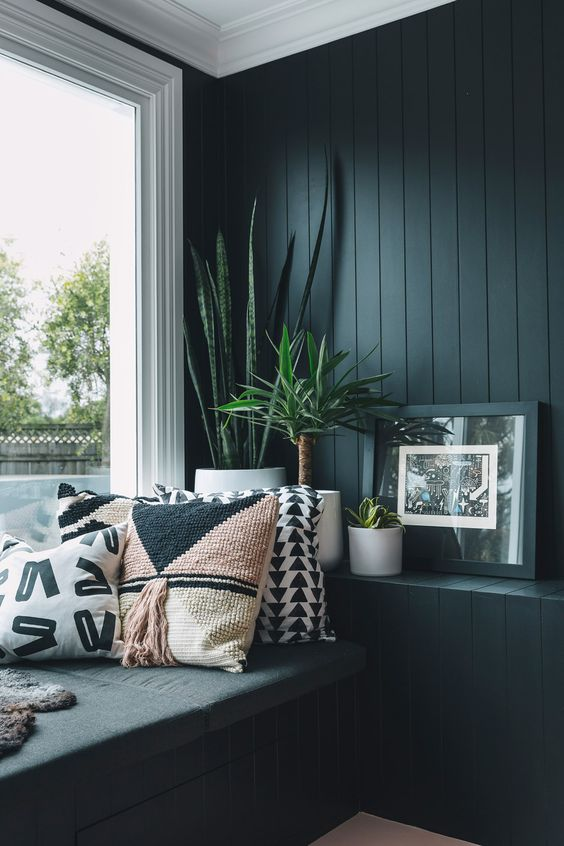 a cozy window nook with a black beadboard wall, a windowsill daybed and a large window plus potted plants