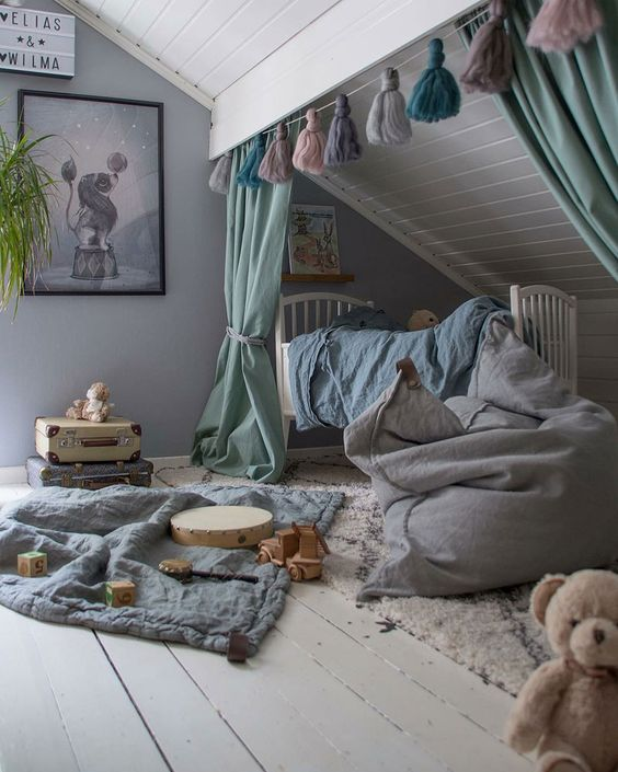a creative attic nursery with muted color textiles, layered rugs, a tassel garland, artworks and lots of toys
