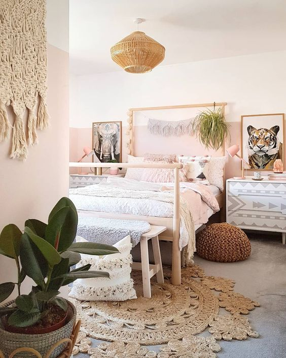 a creative boho bedroom with color block pink walls, a jute rug, a crochet ottoman, greenery and macrame hangings