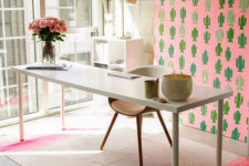 a creative home office with a pink cactus statement artwork, a pink stripe rug and blooms plus neutral furniture