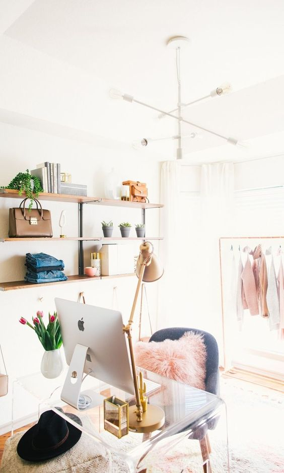a cute and glam cloffice with open shelving, a makeshift closet, a white chandelier, an acrylic desk, a grey chair and touches of pink