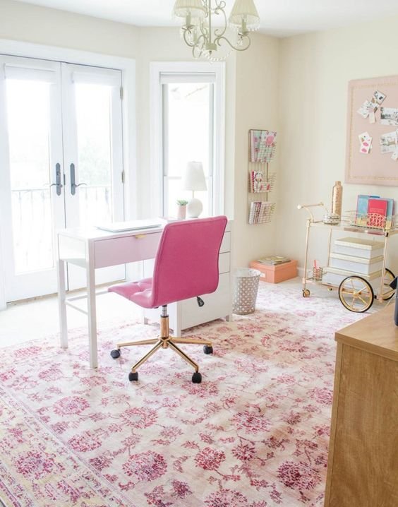 a cute eclectic home office with a hot pink chair, floral printed pink rug and some more accessories that add a girlish feel