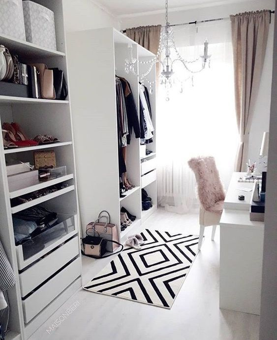 a cute white cloffice with a makeshift closet, a white desk, a pink fur chair, a crystal chandelier, light pink curtains and a graphic rug