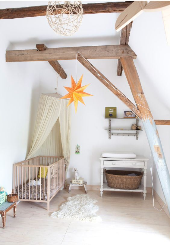 a dreamy attic nursery with wooden beams, vintage furniture, a canopy, stars and baskets plus a cute rug