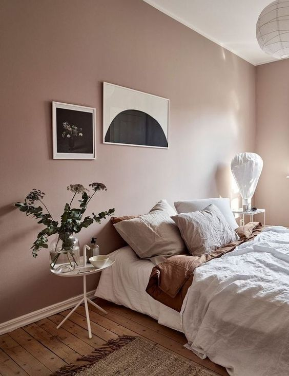 a dreamy bedroom with blush walls, muted color bedding, greenery and a monochromatic gallery wall