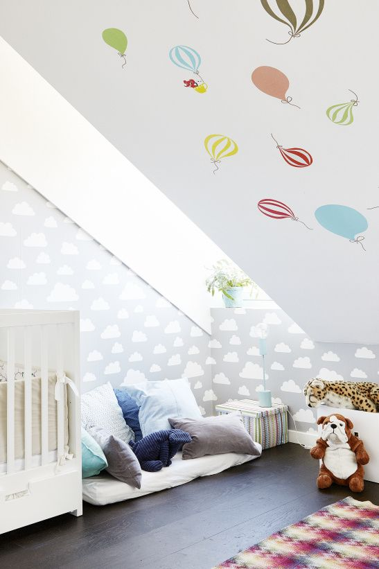 a fun attic nursery with colorful pillows, a hot air balloon wall, a cloud wall and some bold toys