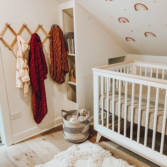 a fun nursery with a rainbow printed wall, a small crib, bright textiles and a storage unit by the bed
