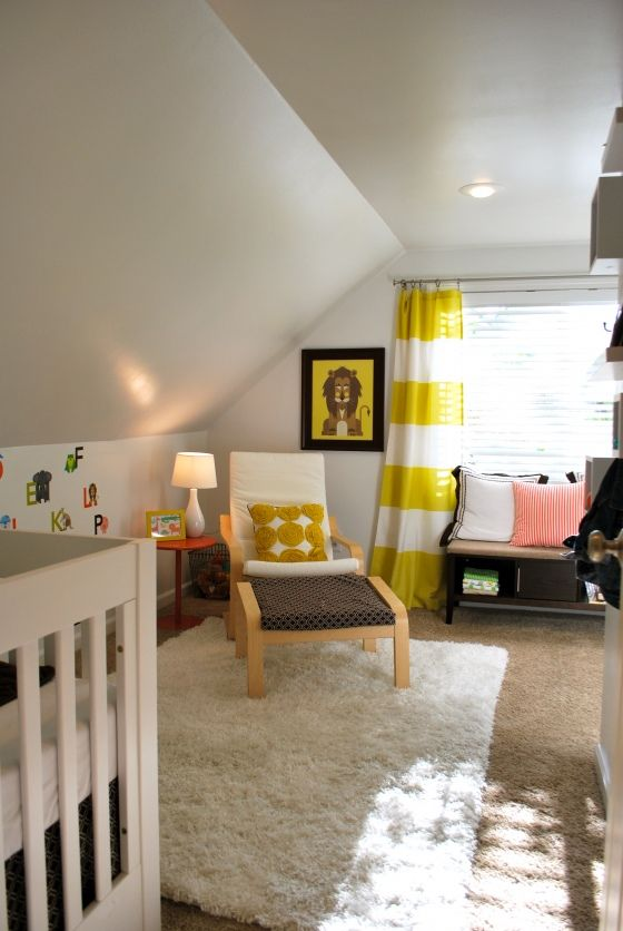 a gender neutral attic nursery with an IKEA chair, crib, bright yellow and black touches and bright pillows