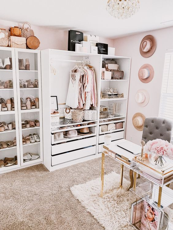 a girlish cloffice with a white makeshift closet, hats on the wall, a crystal chandelier, a catchy acrylic desk and a storage unit