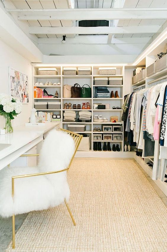 a glam cloffice with a neutral rug, a large open closet, a white double desk, a gold and white fur chair