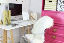 a glam home office with a hot pink storage unit and a pink and gold glitter garland plus an acrylic chair