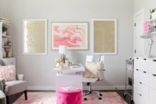 a glam home office with a pink printed rug, gold and pink gallery walls, a hot pink ottoman and a fluffy pillow