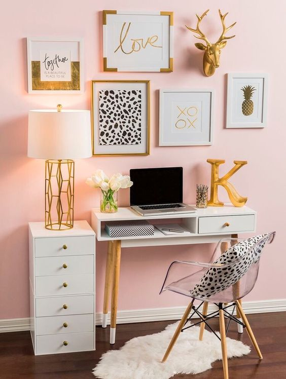 a glam home office with pink walls, an acrylic chair, a pretty gallery wall in gold, black and white