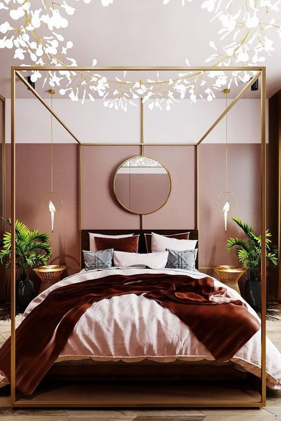 a gorgeous glam bedroom with pink color block walls, a brass bed, a cool chandelier, greeneyr in pots and parrot pendant lamps