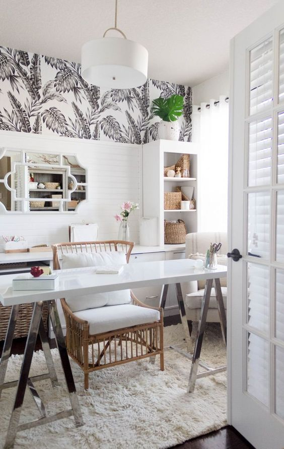 a mid-century modern tropical home office in white, with tropical wlalpaper, rattan furniture, lots of baskets for storage