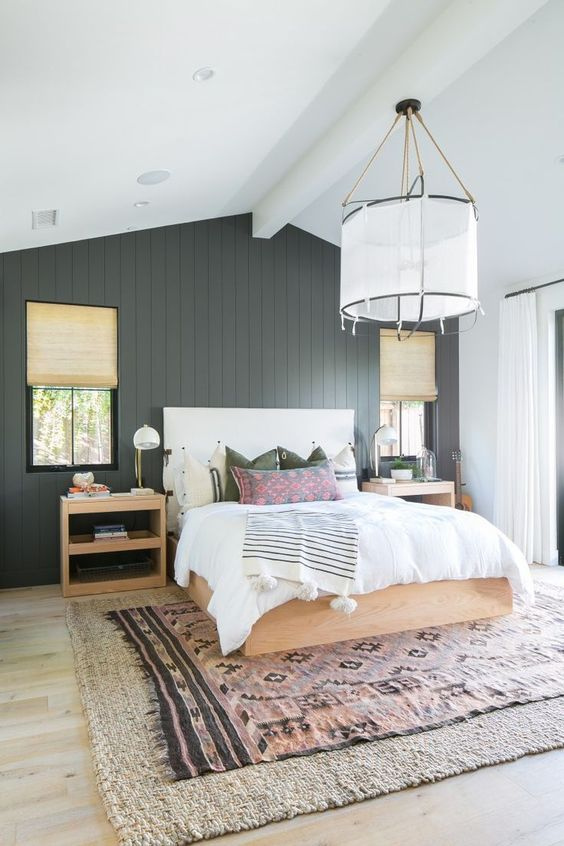 a modern farmhouse bedroom with a black beadboard wall, light stained furniture, much natural light and layered rugs