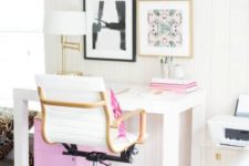 a modern home office with touches of pink – in the gallery wall, books, a pillow and a storage unit under the desk